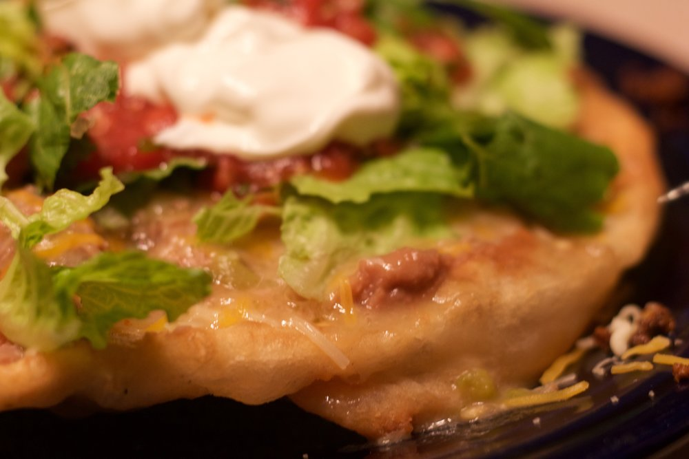 Top with refried beans, seasoned ground beef, green chile, lettuce, fresh salsa & sour cream.