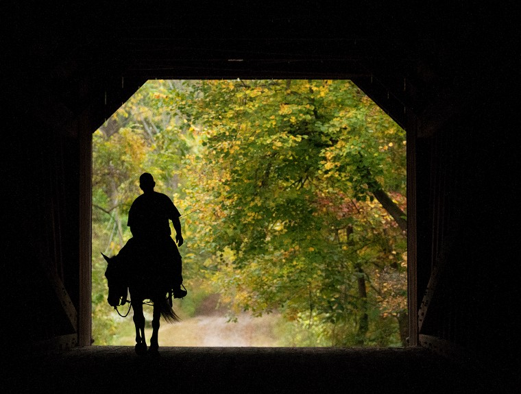 Gary Martin and his horse Snookie of Doylestown Township trot over the Neshaminy Creek via the Schofield Ford Covered Bridge in Tyler State Park on a fall evening in 2013 at sunset.