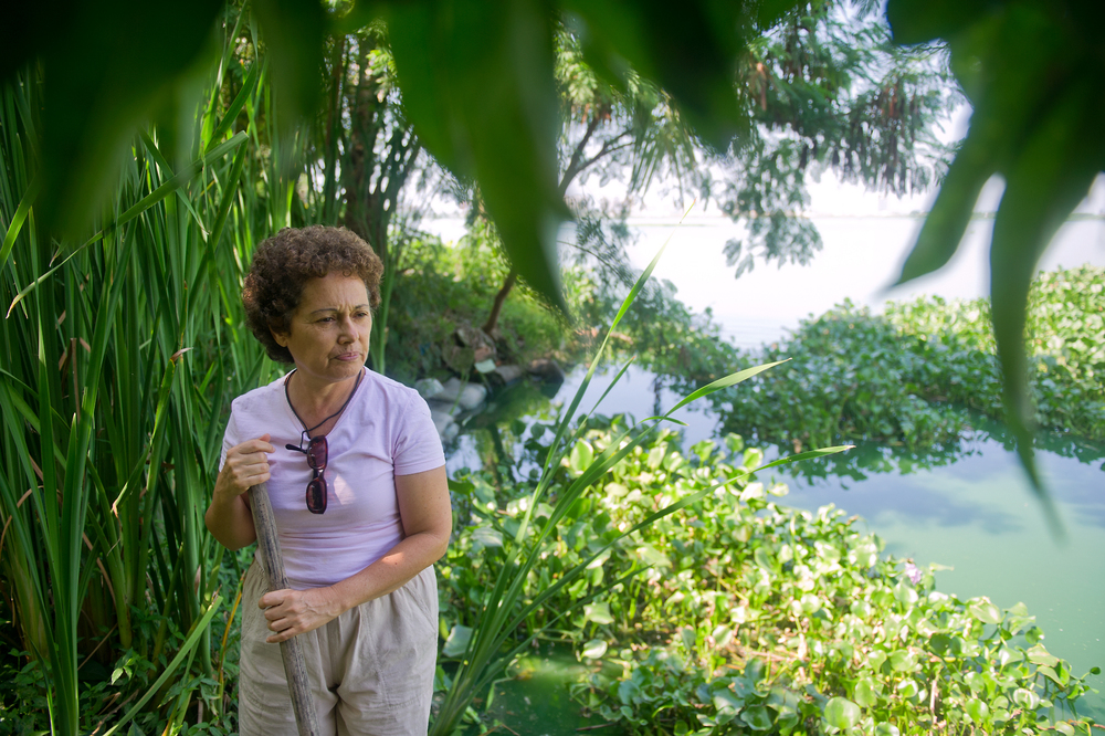 Inalva Mendes Brito, 65, takes a moment in her backyard by the lagoon in Vila Autodromo, a favela in Rio de Janeiro, Brazil. Every day, Inalva comes to the lagoon to dispose of litter that gets trapped in the plants that are in her yard.  Rock in Rio, a concert arena that was built directly across the lagoon, among other things, have caused direct pollution of her land. Prior to these images, in looking ahead to the 2016 Olympics, the government had made numerous attempts to evict the people who lived in this favela, or shantytown.  Inalva was one of those who continued to resist the evictions.