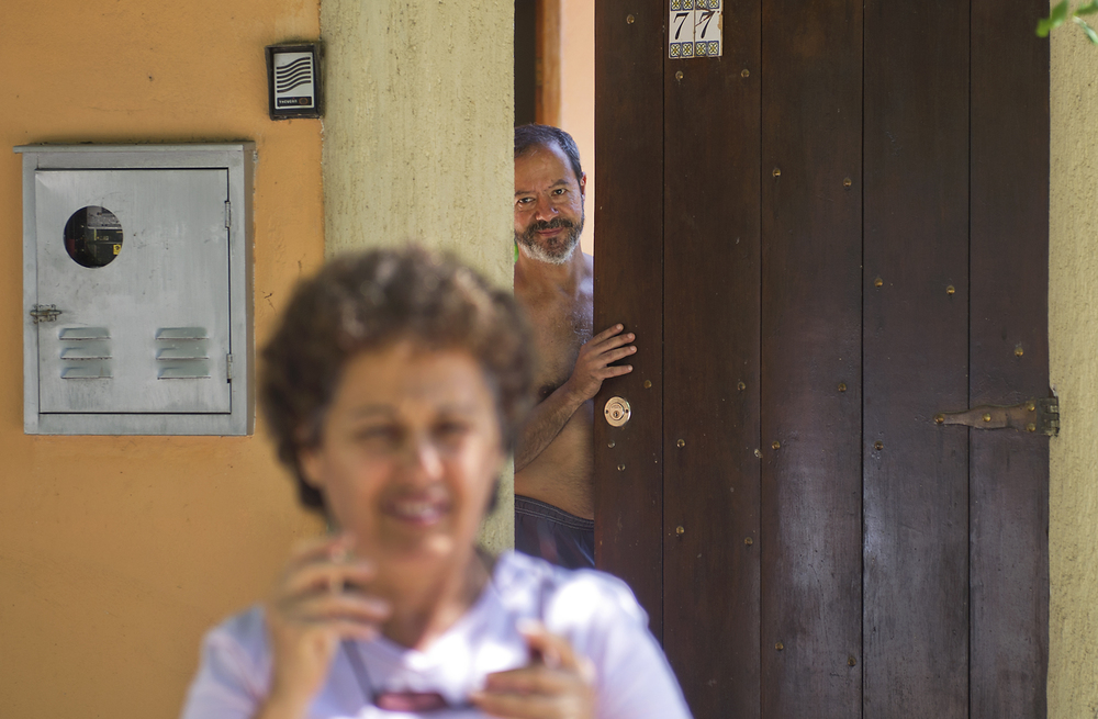 Inalva's husband Elias Serafim watches her leave their home in Vila Autodromo in Rio de Janeiro, Brazil. Brito says if the government has its way this time, one day, when Brito leaves home, she will be unable to return.