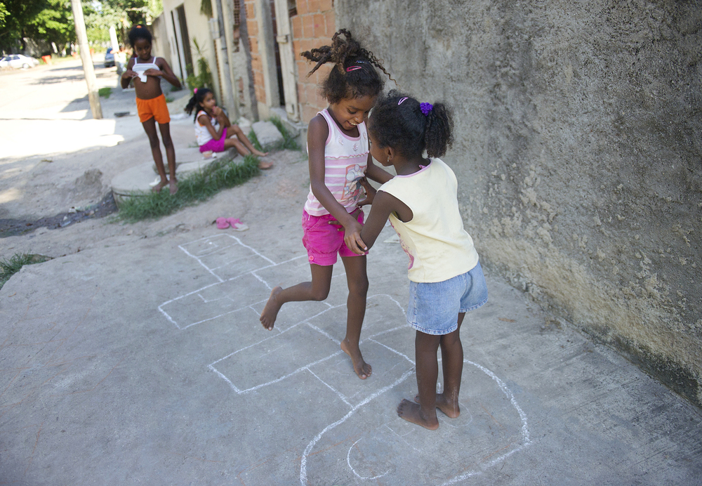 From right,  sisters Joyce, 6, and Raissa, 7, giggle and embrace during a game of hopscotch while cousin Maria Eduarda, 6, and sister Thamires, 10 watch in the background. The girls live in Vila Autodromo in Rio de Janeiro, Brazil, a favela that the city is trying to evict because it lays in the plans for Olympic redevelopment for the 2016 games.