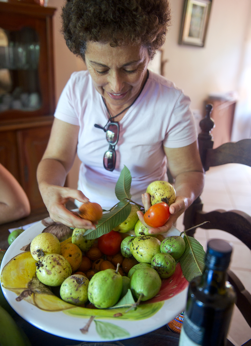 Brito picks fruit that came from her trees outside. Everything that Brito grows is organic.