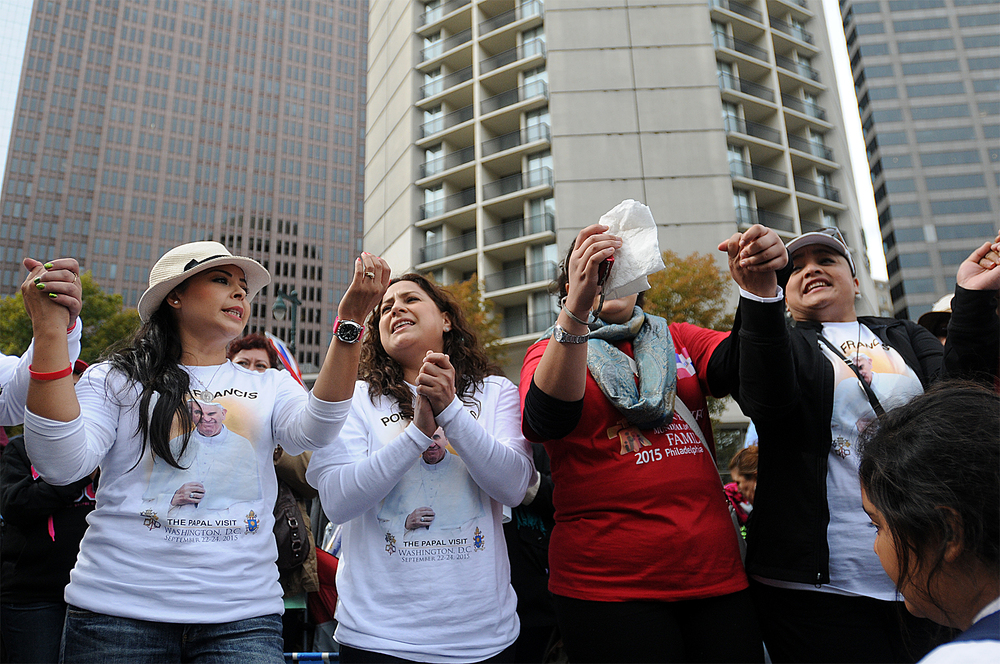 From left: Nora Garcia, Rocio Dardon, Laura Gonzalez and Noriza Escalante, all of Los Angeles, California, sing a song about Pope Francis while waiting to see him arrive via jumbotrons to Cathedral Basilica of Saints Peter and Paul on the Ben Franklin Parkway on September 26, 2015 during the World Meeting of Families.