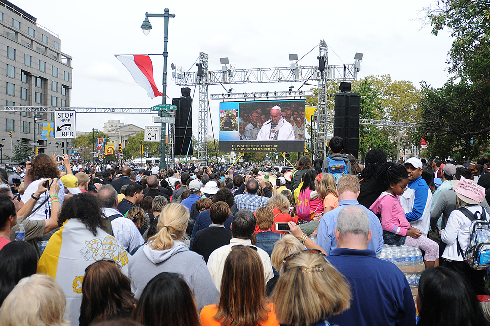 People watch Pope Francis' mass at Cathedral Basilica of Saints Peter and Paul from jumbotrons on the Ben Franklin Parkway on September 26, 2015.on jumbotrons on the Ben Franklin Parkway on September 26, 2015.