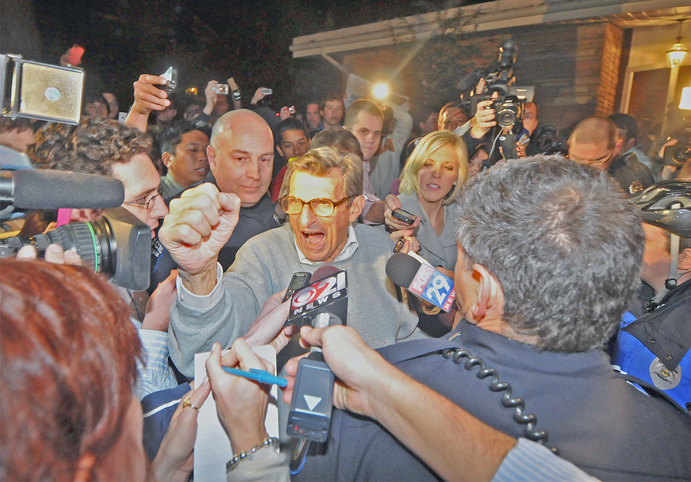 "Head coach Joe Paterno finishes the ""We Are"" chant outside of his home in State College on Tuesday night. A group of around 300 students gathered in support of Paterno."