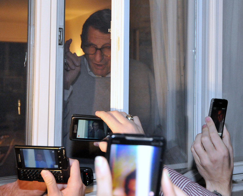 Head coach Joe Paterno speaks to fans and media from inside his window on Tuesday night. A group of about 300 people gathered in support of Paterno.