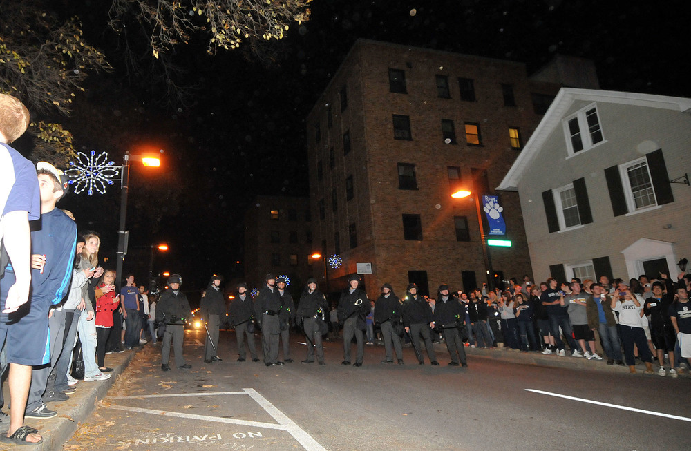 "Policemen line the street of Beaver Avenue on Tuesday night to keep back protesters. They asked for students to clear the street, though many remained on the sidewalk chanting ""USA,"" ""Joe-pa-terno,"" and ""We Are."""
