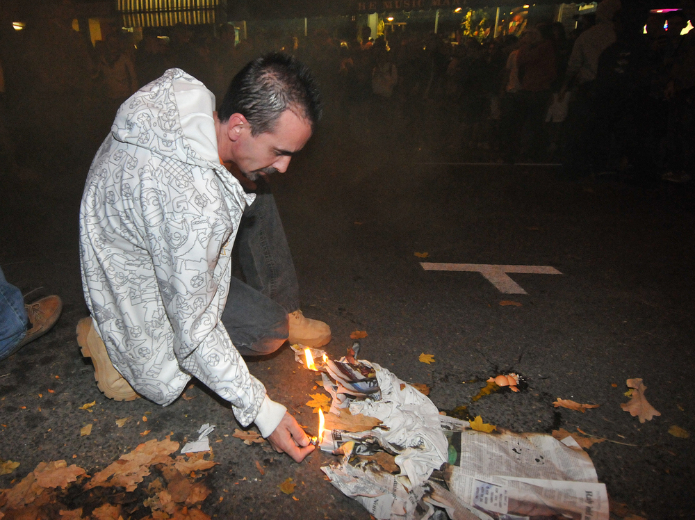 A man sets a shirt and newspaper ablaze on Beaver Avenue during the riots in Beaver Canyon on Thursday night in State College.