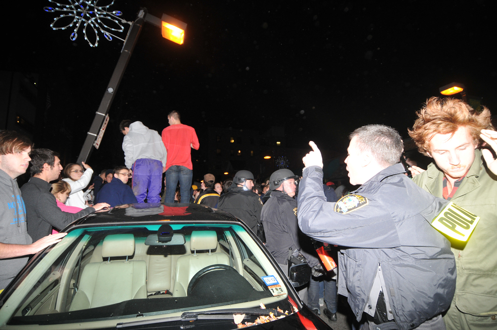 A policeman yells at rioters standing on top of a car in Beaver Canyon Wednesday night.