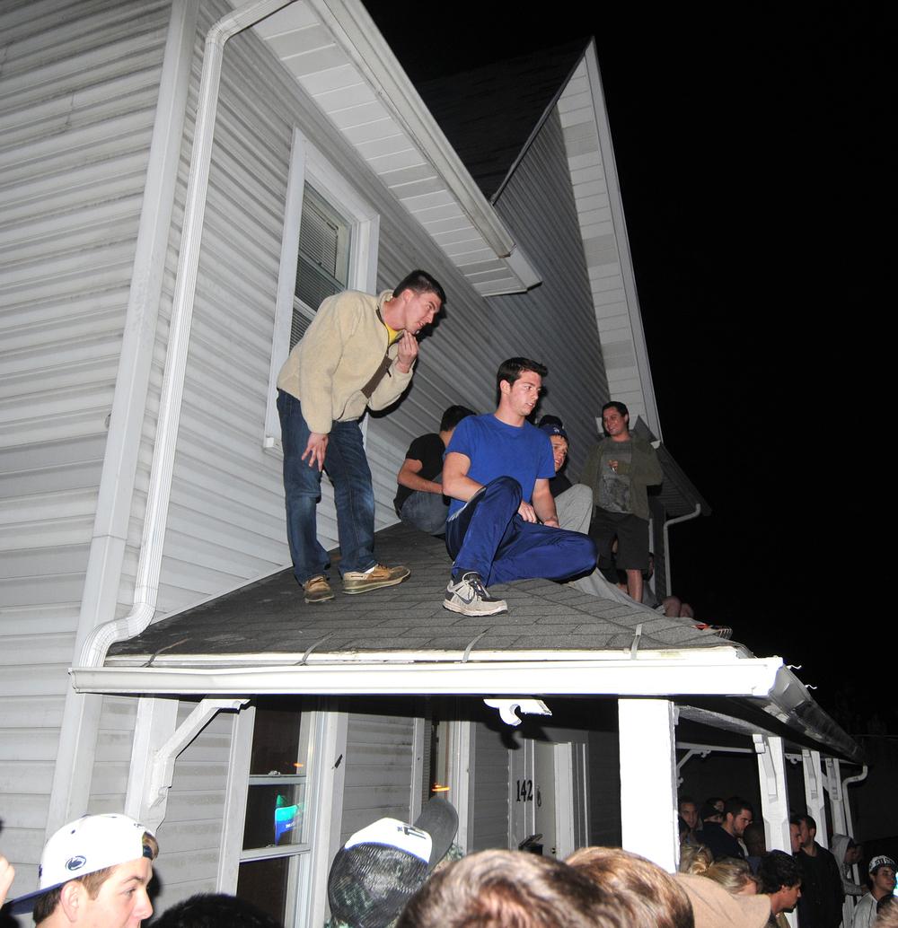 Students sit on the roof of a house at the corner of Beaver and Pugh Street on Wednesday night during the riots.