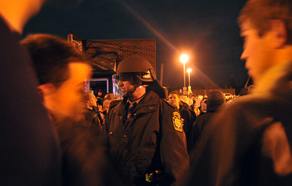A riot policeman stands in line with others to block students from the road on Beaver Avenue during the riots on Wednesday night. The policemen, armed with nightsticks, mace and pepper spray formed lines to keep students on the sidewalks and off the street.