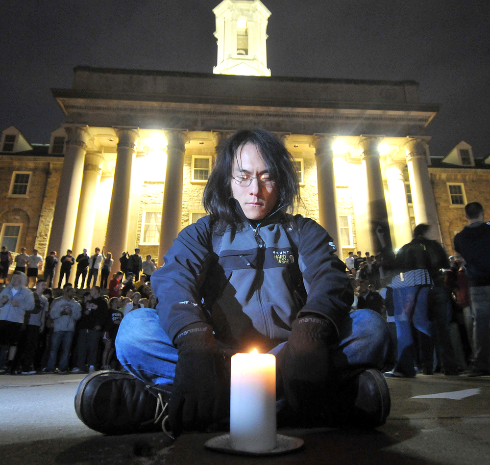 Brenton Mitchell, 28, of State College, sits on the ground with a candle at Old Main during the beginning of the riot in State College on Wednesday night. The crowd gathered here and then moved downtown. Mitchell got stepped on multiple times.