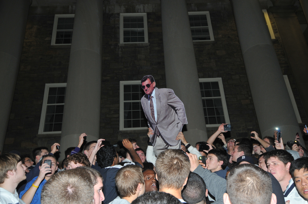Students riot with a cardboard Joe Paterno on the steps of Old Main on Wednesday night in response to his termination as the head coach of football.