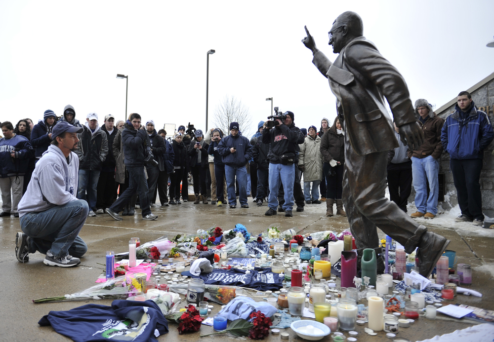 A mourner kneels in front of the Joe Paterno statue on Sunday, Jan. 22, 2012 where a crowd had gathered upon hearing news of his death.