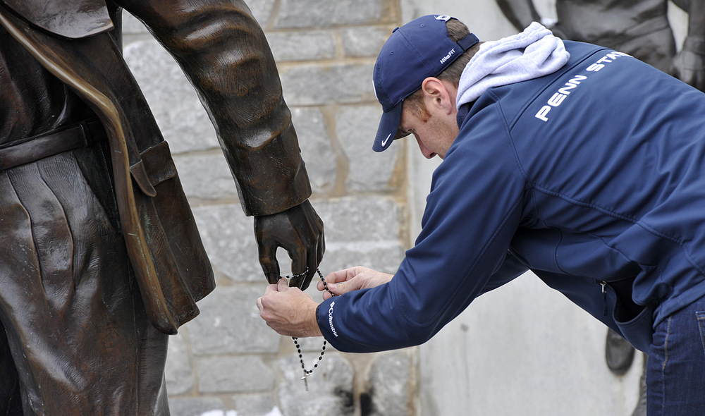 A mourner places a rosary around the hand of the Joe Paterno statue on Sunday, Jan. 22, 2011 outside of Beaver Stadium. A crowd had gathered after hearing the news that Paterno had passed away in the morning.
