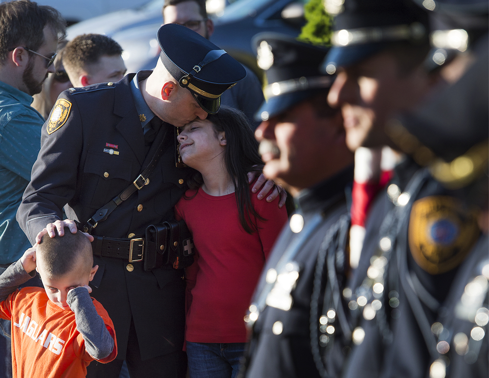 Falls Township Police Lieutenant Nelson Whitney kisses daughter Abigail, 12, with a gentle hand on son Ethan, 6, just two of his five children, before a county-wide blue mass at St. Andrew Catholic Church in Newtown Township on Monday, May 16, 2016.
