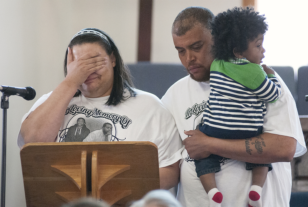 Te-Shawn Wilson, sister of July 2014 triple-shooting victim Tyrone Moss, is overcome with emotion while standing with Vincent Moss and little cousin Josiah McClain, 1, while trying to speak to the group gathered at the House of Prayer Church in Bristol Township about gun violence on Sunday, April 19, 2015. Community marched from Norton Avenue Baptist Church to the House of Prayer Church to pray and walk to honor the memories of those who have lost loved ones to gun violence. A small service was held at the House of Prayer for speakers to talk about loved ones who have become victims of gun violence.