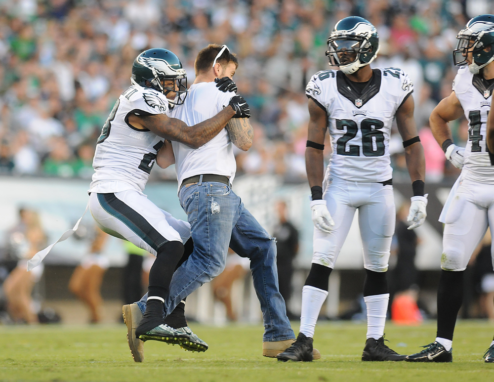 Eagles cornback Nolan Carroll (23) tackles a fan who rushed the field during their game against the Cowboys on Sunday, September 20, 2015 at Lincoln Financial Field.