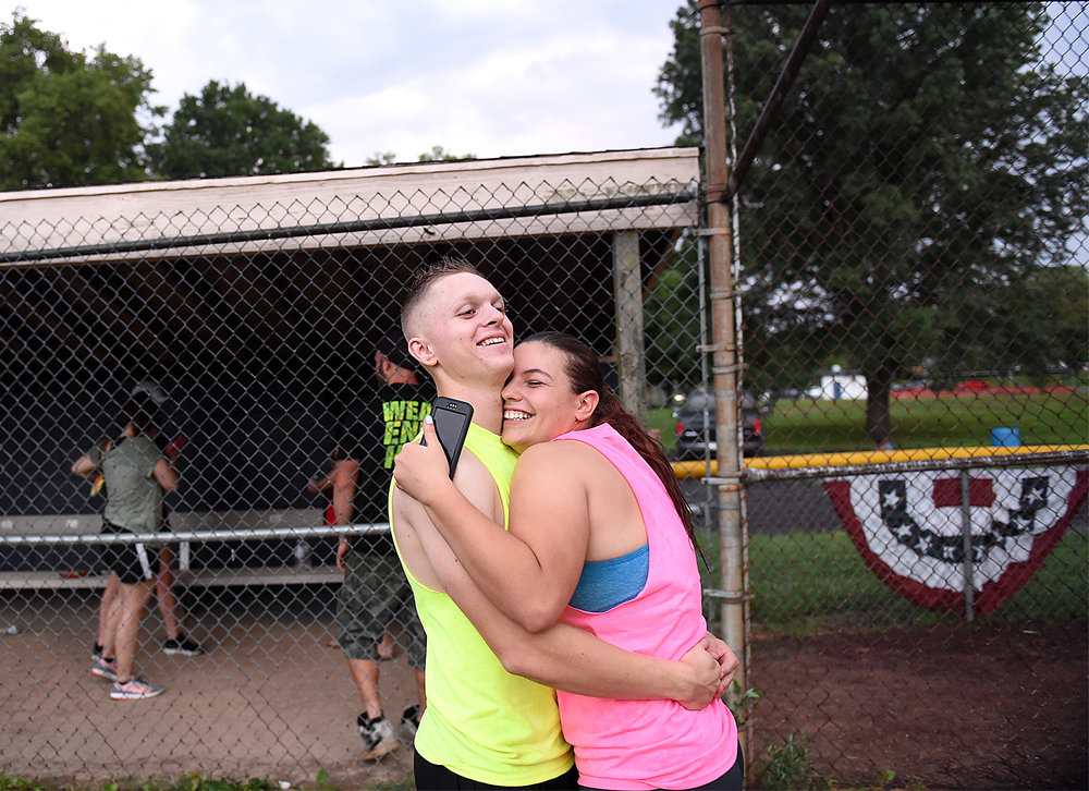 "Deidra ""Dee"" Hubay, 18, originally of Middletown Township, hugs her then fiancé and now husband Dan Bryan, 19, also originally of Middletown Township, while playing kickball with family friends on Tuesday, July 21, 2015 at Williamson Park in Morrisville.  Bryan was on break from his MOS school for his Marine Corps job training, which was in Cory Station Pensacola, FL, and Goodfellow Air Force Base in San Angelo, TX. Hubay had yet to leave for her boot camp. Both were a part of the DEP, or Delayed Entry Program, for the Marine Corps."
