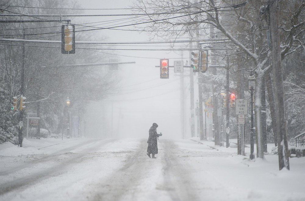 A woman crosses West State Street in Doylestown during the morning snowfall on Thursday, February 9, 2017. Many area schools and businesses were closed because of the snowfall, leaving the street wide open to pedestrians.