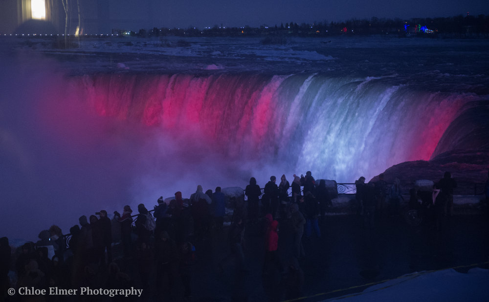 Falls at night. Niagara was red and white for Canada, New York was red, white and blue for USA.