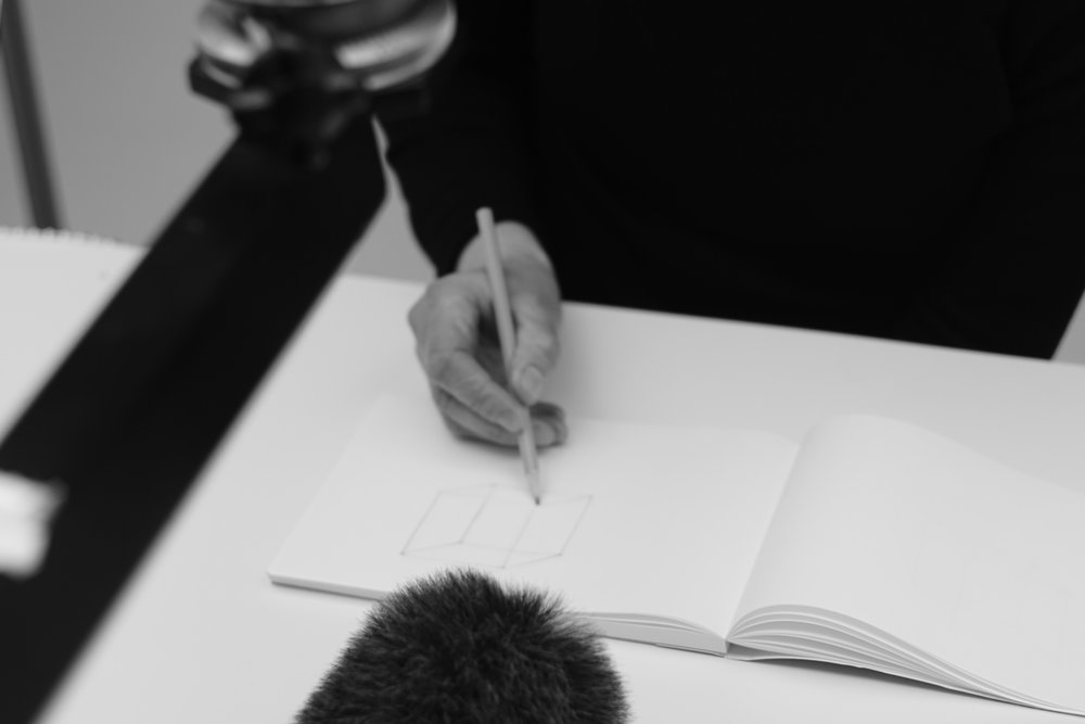 Drawing the perfect cube, still from the process, drawing a cube on each page in a notebook.