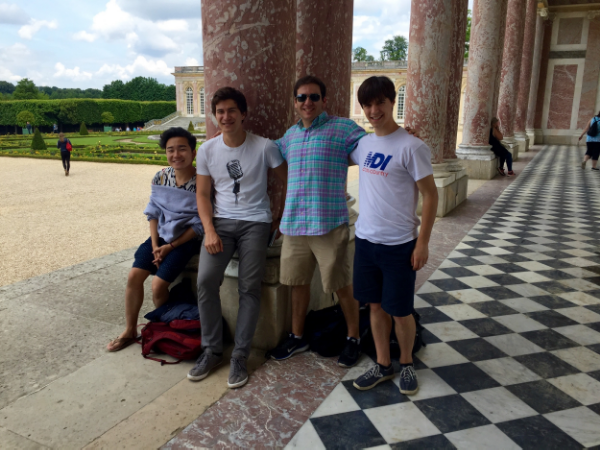 Some Dins posing by beautiful columns of colored marble at Versailles