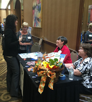 Patty Outten, Carolyn Stark, and Cara Richardson discuss RTI2-Behavior with a conference attendee.