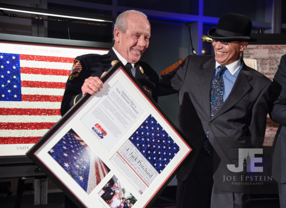 Marcos Antonio presents Captain Jack Pritchard, legendary NYC firefighter and star #4 on the Flag For Hope, with his serigraph and certificate of authenticity
