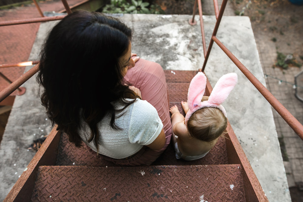 baby hangs on fire escape with mom wearing pink bunny ears-(ZF-0126-04493-1-017).jpg