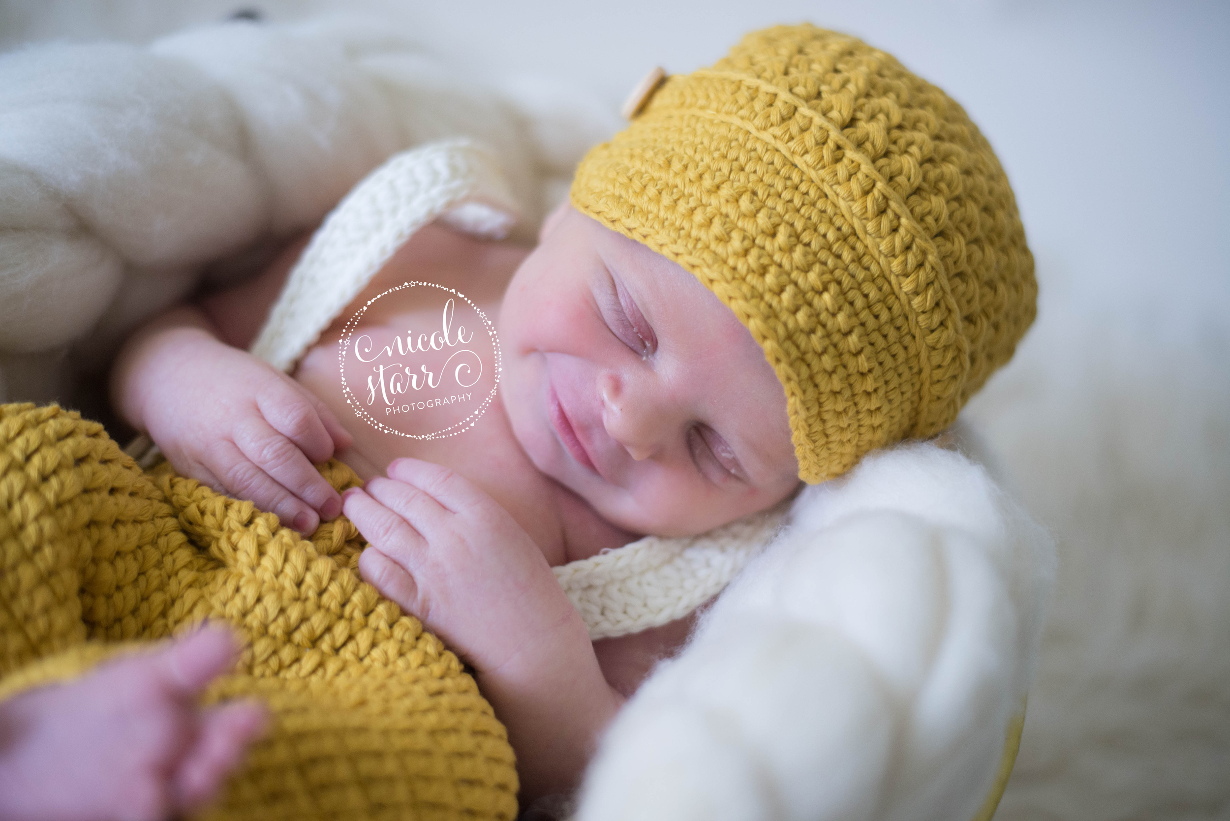 newborn photo with crocheted pageboy hat and suspenders and pants