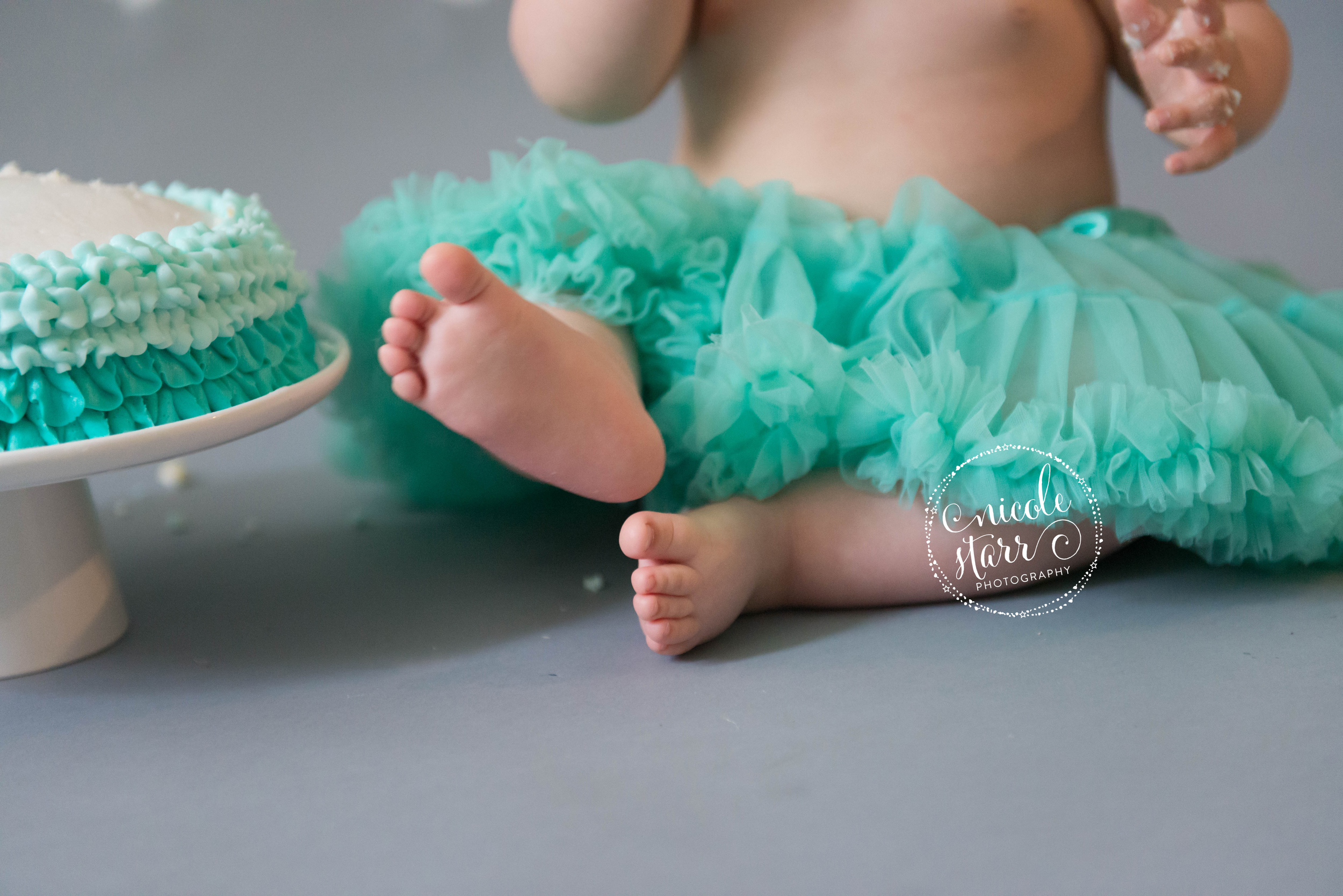 baby toes and birthday cake with teal tutu and teal frosting
