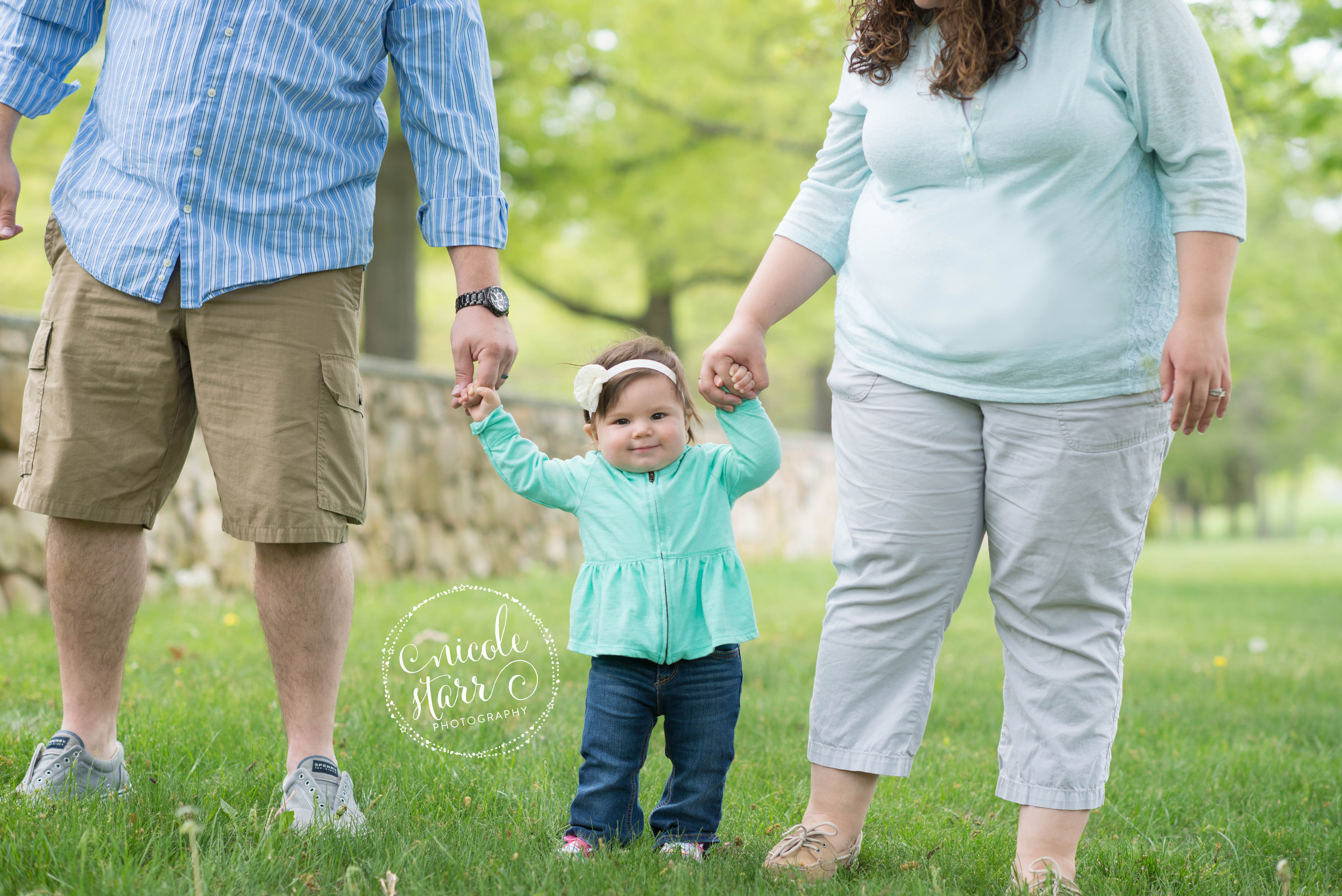 baby taking first steps in family photo with mom and dad
