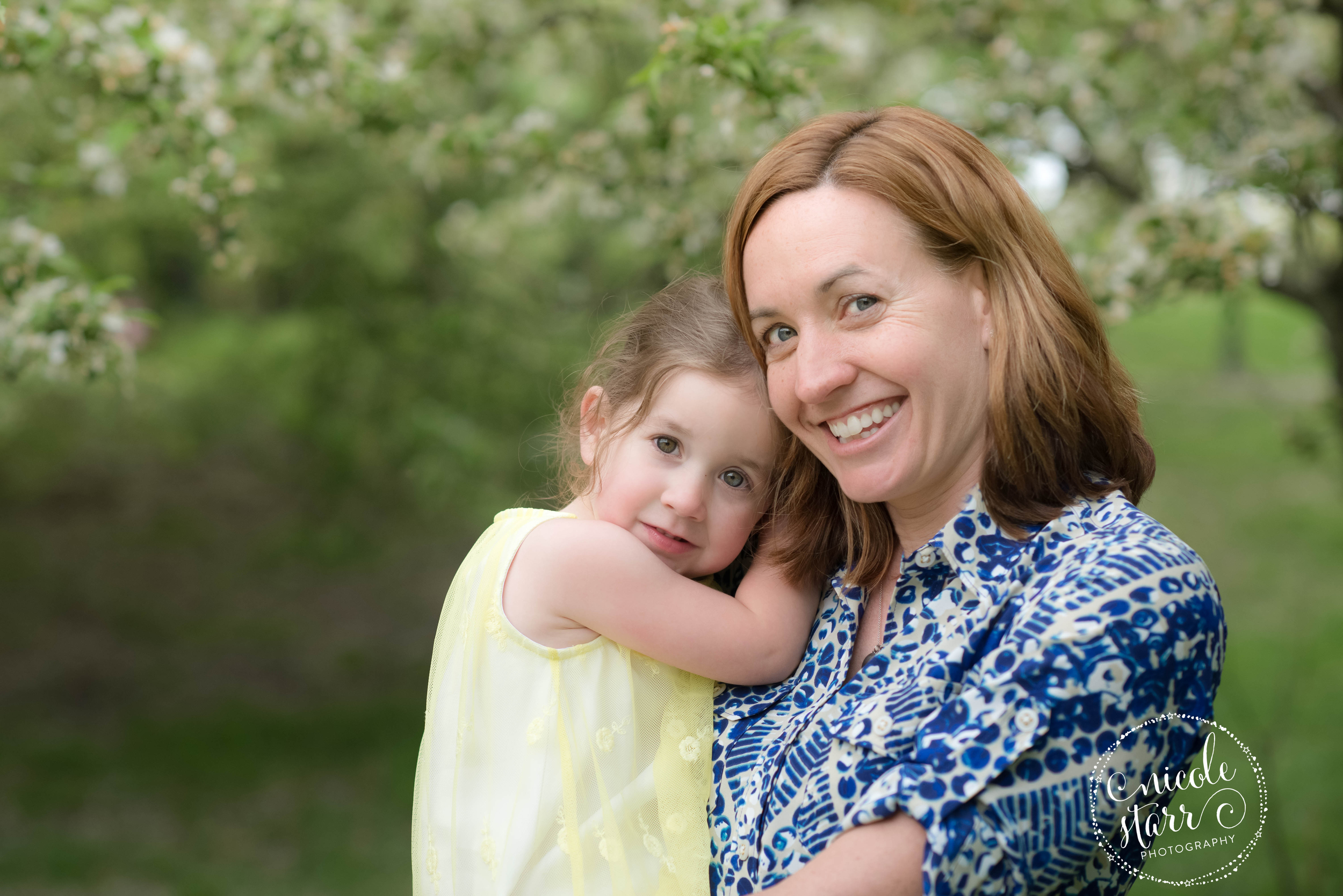 mother and daughter portrait with springtime blossoming tree