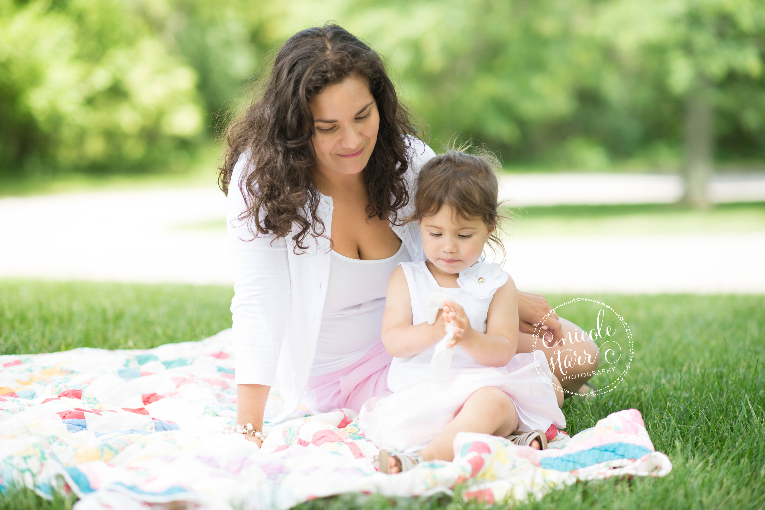 mommy and baby girl in a park on a quilt reading a book