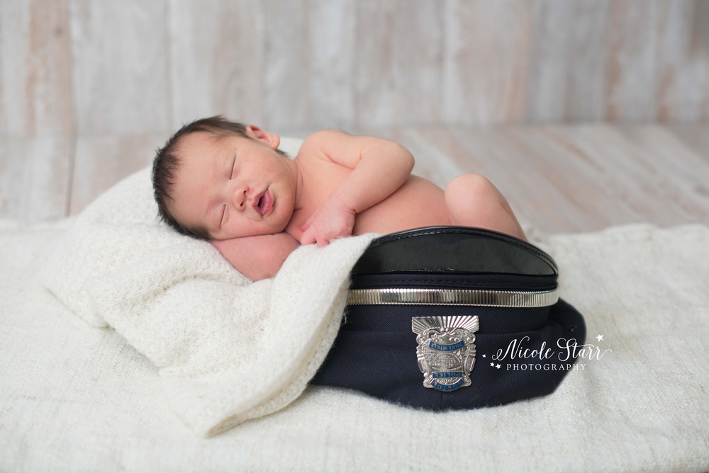 newborn baby in a police hat with Saratoga and Albany newborn photographer Nicole Starr Photography