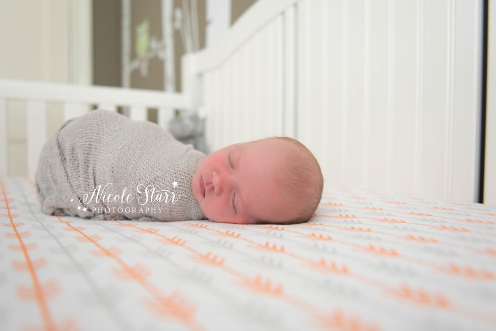 lifestyle newborn session in crib.jpg