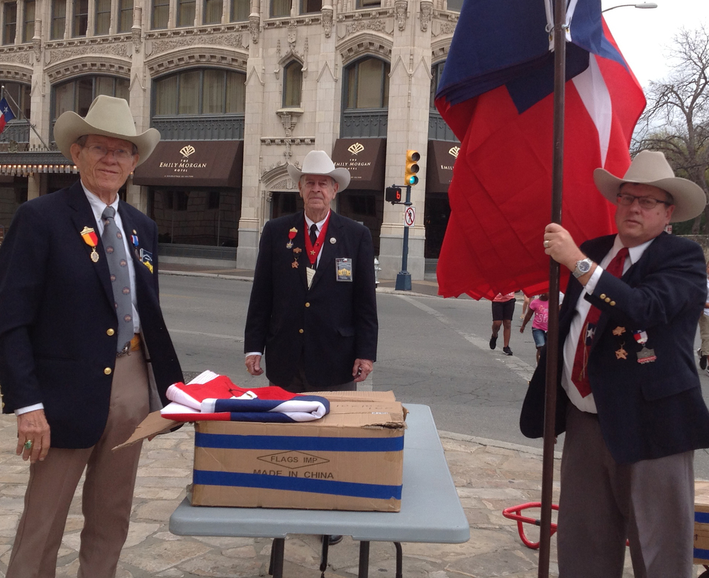 Robert Fletcher  ,   Tommie Wood   &   Christopher Lancaster   hoist flags at the original location of the north wall; a few steps away from where Alamo Commander Lt. Col. William Barret Travis's lost his life during the battle.