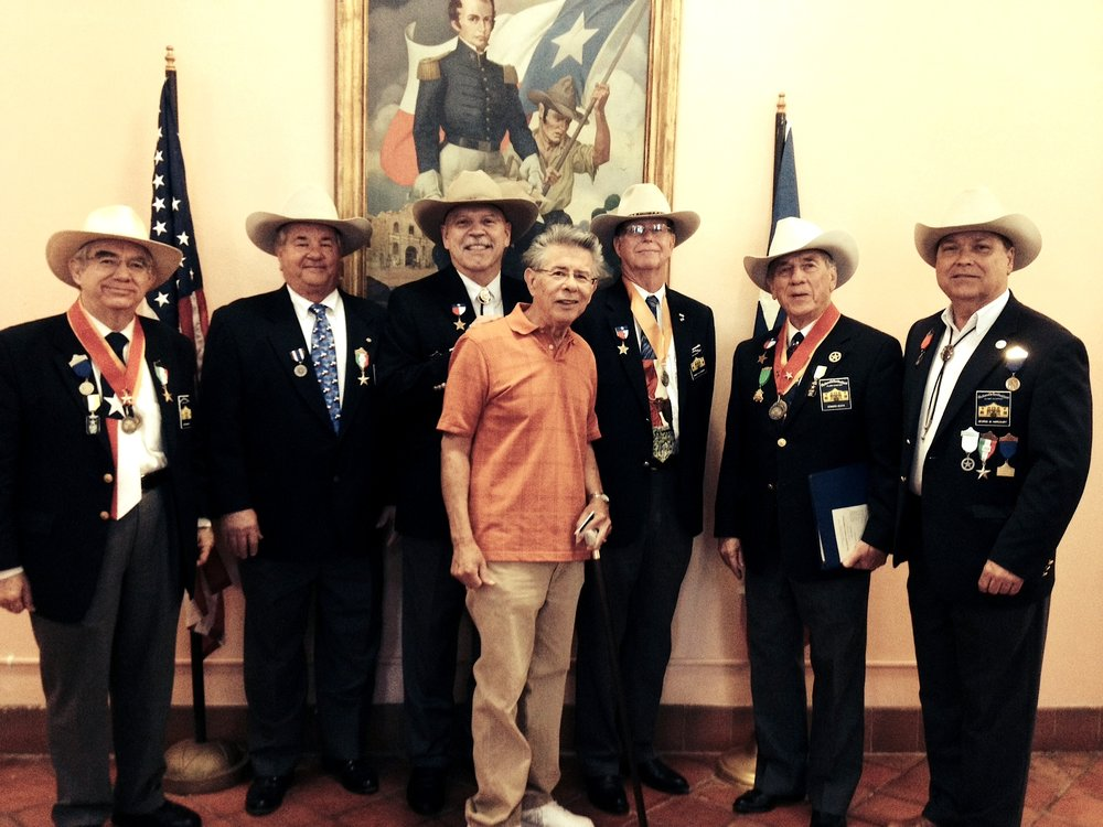 Chapter members   Bob Benavides  ,   Al Davis  ,   Joe Weathersby  ,   Nick Martinez  ,   Ken Pfeiffer  ,   Ed Heath   &  President    George Harcourt   poise in front of a portrait of William Barret Travis in Alamo Hall.