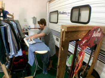 A women Ironing her and her husbands clothes, inside the RV they share, after leaving their home to find employment in Watford City ND. (Credit:  Tom Haines )