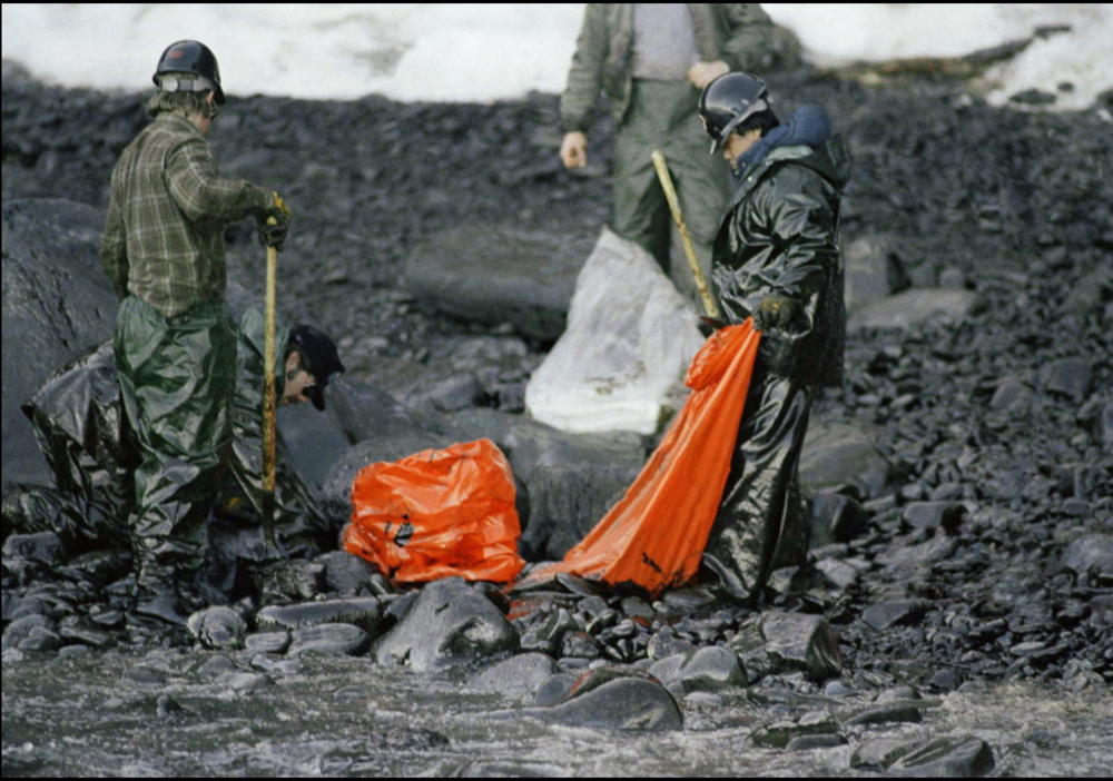 Workers try to remove globs of oil from Naked Island in Prince William Sound, Alaska, in April 1989.   Image credit: Jack Smith/Associated Press