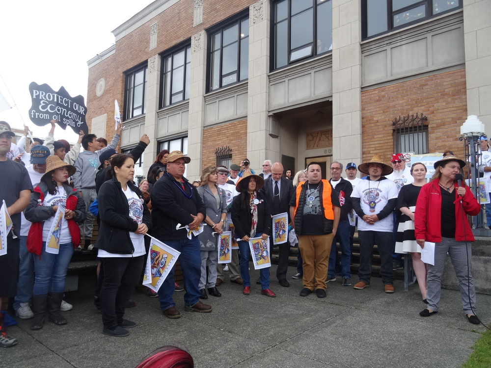 "Quinault President Fawn Sharp (right) and Vice-President Tyson Johnston (5th from right) host the ""Shared Waters, Shared Values"" rally on July 8, 2016, with representatives from the Lummi, Quileute and Makah tribes, Hoquiam Mayor Jasmine Dickhoff (2nd from right), other local officials, and leaders of fishing associations and local environmental groups (Credit: Zoltan Grossman)."