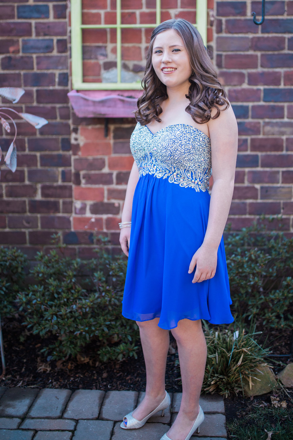 Girl in pretty blue dress with rustic window and brick wall