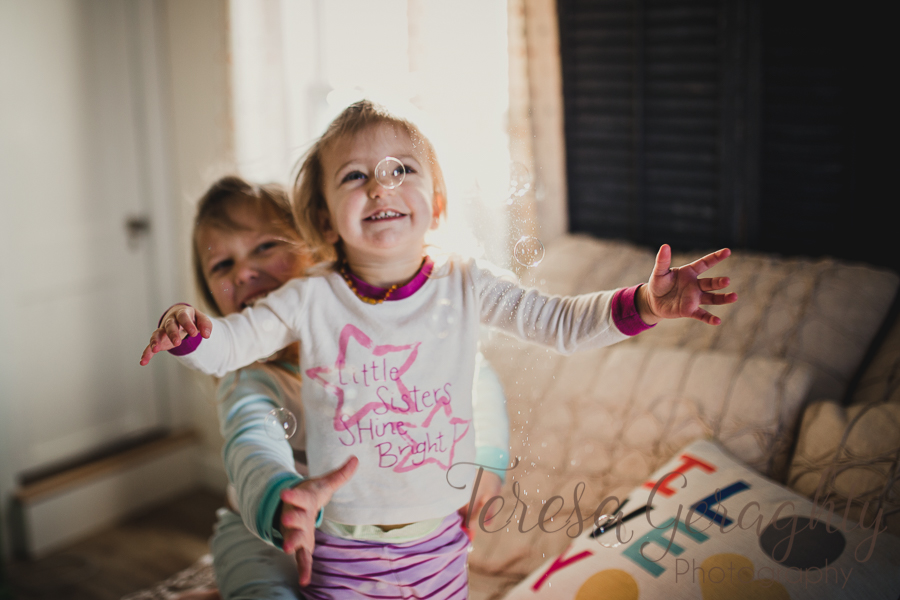 girls playing with bubbles on the bed