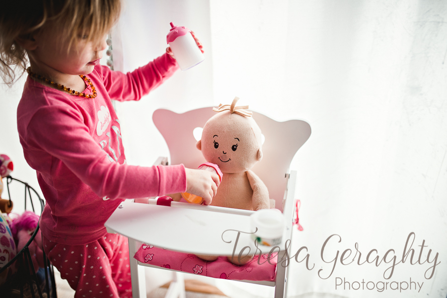 toddler feeding baby doll a bottle in highchair