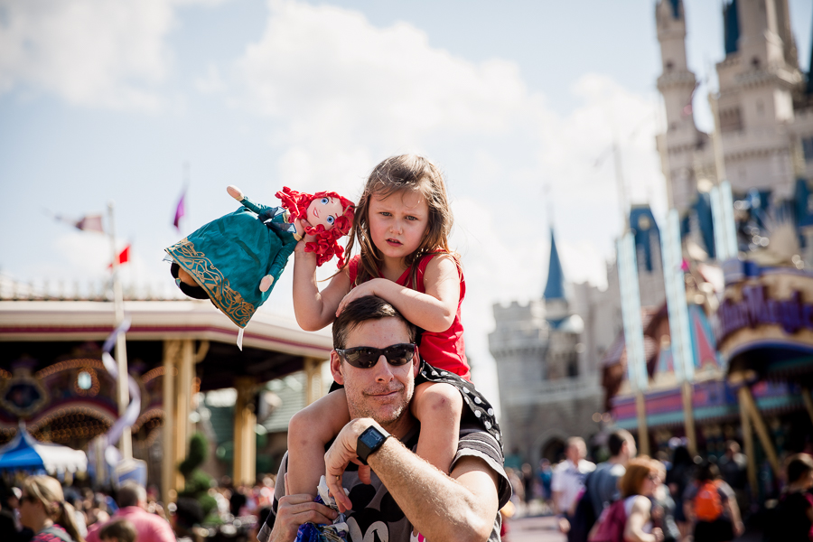 girl on dad's shoulders at disney