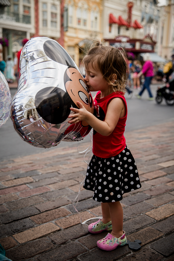 girl kissing mickey balloon