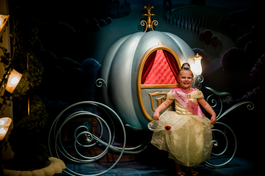 girl at bippity boppiti boutique in front of cinderella's carriage