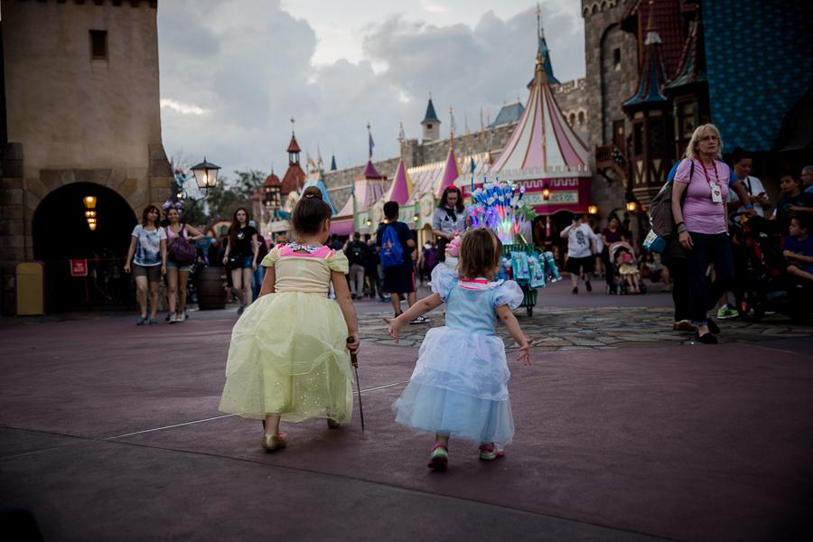 sisters walking in princess dresses in magic kingdom