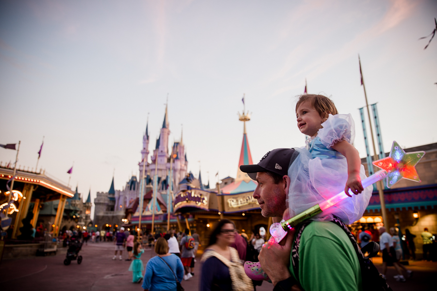 girl on dad's shoulders at magic kingdom